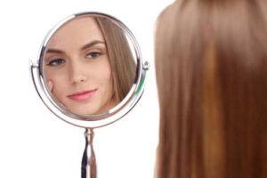 鏡で目元をチェックしている女性