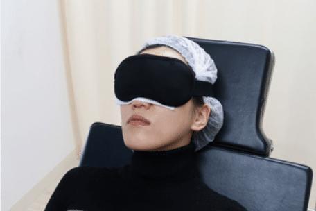 術後にアイスノンを使用して目元を冷やしている女性